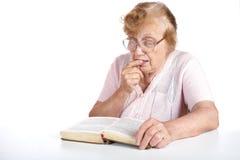 L'anziana in vetri legge il libro Immagine Stock Libera da Diritti