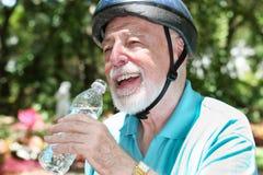 L'anziano attivo beve l'acqua Fotografia Stock