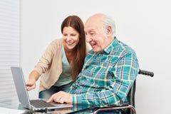 L'anziano con il computer portatile sta facendo un corso di computer fotografia stock