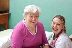 L'anziano ed il medico stanno sorridendo Fotografie Stock Libere da Diritti