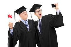 L'anziano ed il tipo nella graduazione abbiglia la presa del selfie Immagine Stock Libera da Diritti