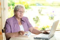 L'anziano femminile con soldi sta utilizzando il computer Immagine Stock