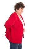 L'anziano femminile isolato nel rosso ha il mal di schiena o reumatismo immagine stock