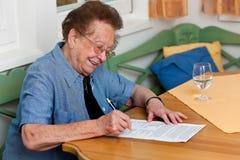 L'anziano firma un contratto immagine stock