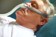 L'anziano prende un pelo facendo uso del dispositivo di CPAP Fotografia Stock