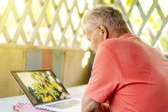 L'anziano anziano si è ritirato l'uomo che lavora ad un computer portatile nell'alcova dell'estate fotografia stock