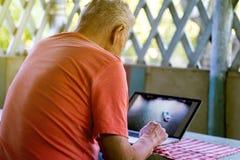 L'anziano anziano si è ritirato l'uomo che lavora ad un computer portatile nell'alcova dell'estate fotografia stock libera da diritti