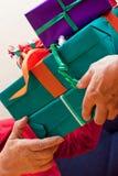 L'anziano si siede ed ottiene o dà molti il primo piano dei regali Fotografie Stock