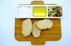 L'aperitivo con sale, olio d'oliva, peperoni e la cipolla incide i dadi fotografie stock libere da diritti