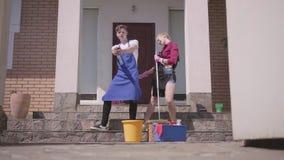 L'apertura del portone e la giovane donna e l'uomo positivi che ballano sul portico della casa Coppia fare piazza pulita insieme video d archivio