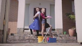 L'apertura del portone e la giovane donna e l'uomo positivi in guanti ed in grembiuli che posano sul portico della casa Pulizia stock footage