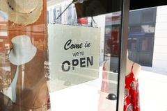 L'apertura di affari con l'entrata aperta firma dentro il negozio della via attraverso il vetro Immagine Stock