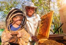 L'apicoltore del nonno passa alla sua esperienza il piccolo nipote immagini stock libere da diritti