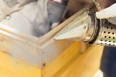 L'apicoltore sta lavorando con le api e gli alveari sull'arnia Il fumatore dell'ape è usato - strumento degli apicoltori per tene immagini stock libere da diritti