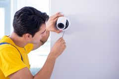 L'appaltatore che installa le macchine fotografiche del cctv di sorveglianza nell'ufficio fotografia stock libera da diritti