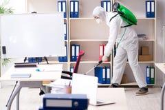 L'appaltatore professionale che fa controllo dei parassiti all'ufficio fotografia stock