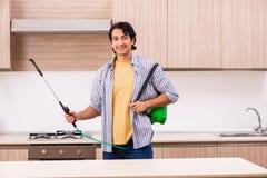 L'appaltatore professionale che fa controllo dei parassiti alla cucina fotografia stock libera da diritti