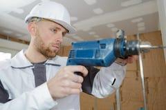 L'appaltatore utilizza il martello pneumatico per perforare il muro di cemento fotografia stock libera da diritti