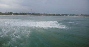 L'appareil-photo de bourdon tourne à gauche pour suivre le ressac énorme atteignant la plage tropicale paisible et se brisant ave clips vidéos