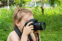 L'appareil-photo de SLR dans le girl& x27 ; mains de s Images libres de droits