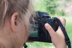 L'appareil-photo de SLR dans le girl& x27 ; mains de s Photographie stock libre de droits