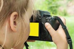 L'appareil-photo de SLR dans le girl& x27 ; mains de s Photo libre de droits
