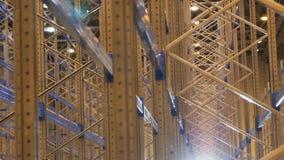 L'appareil-photo montre de grands supports brillants modernes en métal dans l'entrepôt vide banque de vidéos