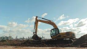 L'appareil-photo montre l'excavatrice et l'usine jaunes à l'arrière-plan banque de vidéos