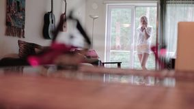 L'appareil-photo montre la pièce légère meublée avec la position blonde mignonne au balcon ouvert clips vidéos
