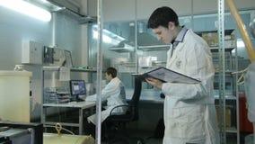 L'appareil-photo montre le jeune assistant de laboratoire regardant l'outil de fonctionnement banque de vidéos