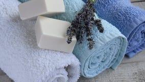 L'appareil-photo se déplace le long des serviettes, du lavand et des savons propres et frais sur le fond en bois banque de vidéos