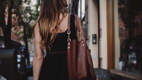 L'appareil-photo suit du jeune blogger féminin de mode avec le sac élégant marchant le long du mouvement lent de belle petite rue banque de vidéos