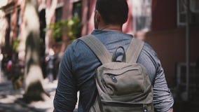L'appareil-photo suit le jeune homme local décontracté avec le sac à dos marchant le long de la rue louche de Brooklyn d'été dans banque de vidéos