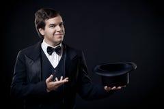 L'apparence de magicien dupe avec le premier chapeau d'isolement sur l'obscurité photo stock