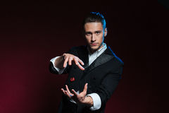 L'apparence sûre de magicien de jeune homme dupe utilisant une matrice volante photo stock