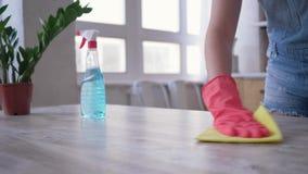 L'appartamento di pulizia, la ragazza in guanti con lo spolveratore ed il detersivo pulisce la tavola nella cucina video d archivio