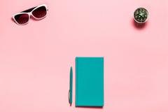 L'appartement créatif étendent la photo du bureau d'espace de travail avec le carnet bleu vert, lunettes, fond de rose de l'espac Photographie stock libre de droits