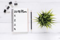 L'appartement créatif étendent la photo du bureau d'espace de travail avec le carnet de liste de nouvelle année de 2018 plans et  Photographie stock libre de droits