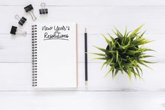L'appartement créatif étendent la photo du bureau d'espace de travail avec le carnet de liste de résolution de nouvelle année et  Image libre de droits