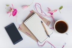 L'appartement créatif étendent la photo du bureau d'espace de travail avec le smartphone, café, le crayon, fleurs avec le fond de Photo stock