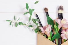 L'appartement décoratif étendent la composition avec les produits de maquillage, l'enveloppe de papier d'emballage et les fleurs  photos stock
