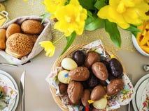 L'appartement de brunch de Pâques s'étendent avec des oeufs de chocolat, des petits pains de pain et des jonquilles jaunes images stock