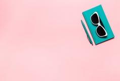 L'appartement de Minimalistic étendent la photo du bureau d'espace de travail avec le carnet bleu vert, lunettes, fond de rose de Photos libres de droits