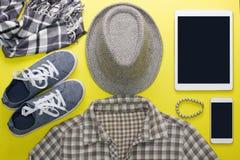 L'appartement du ` s de femme étendent les vêtements gris comprimé et la maquette de téléphone portable Photos stock