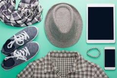 L'appartement du ` s de femme étendent les vêtements gris comprimé et la maquette de téléphone portable Photographie stock libre de droits