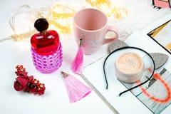 L'appartement femelle s'étendent avec le parfume, la poudre de visage et la tasse de bieg sur le fond blanc photo libre de droits