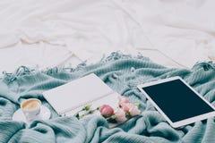L'appartement modifié la tonalité étendent le comprimé, le téléphone, la tasse de café et les fleurs sur la couverture blanche av Image libre de droits