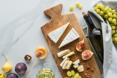 l'appartement s'étendent avec la composition de nourriture du fromage sur le vin et des fruits de miel de planche à découper sur  images libres de droits