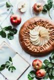 l'appartement s'étendent avec la tarte aux pommes faite maison disposée, le carnet vide, les pommes fraîches et les feuilles vert images stock