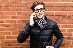 L'appel téléphonique futé de jeunes cellules belles d'homme parlent le sourire au-dessus du mur de briques photographie stock libre de droits